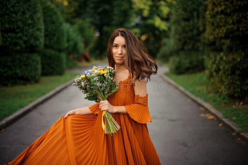 Πορτρέτο της όμορφης γυναίκας στο μακρύ πορτοκαλί φόρεμα στοκ φωτογραφίες