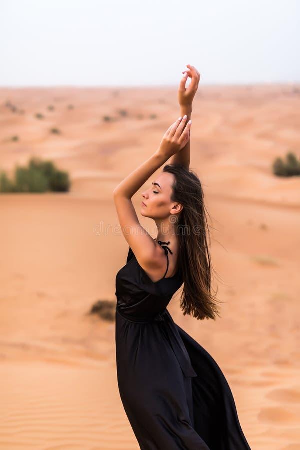 Πορτρέτο της όμορφης γυναίκας τοποθέτηση φορεμάτων πολύ κυματισμού στη μαύρη υπαίθρια στην αμμώδη έρημο στοκ φωτογραφίες