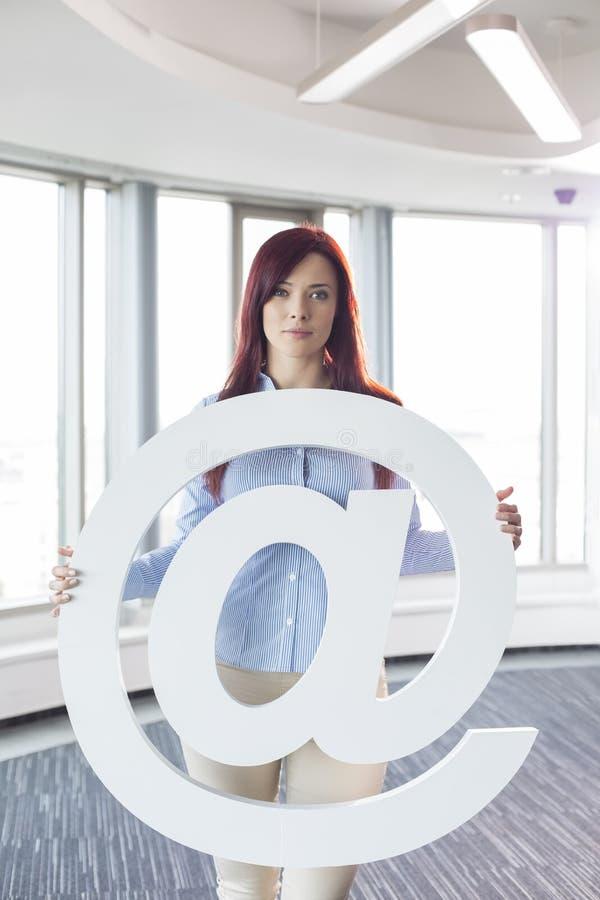 Πορτρέτο της όμορφης εκμετάλλευσης επιχειρηματιών στο σημάδι στο δημιουργικό γραφείο στοκ φωτογραφία με δικαίωμα ελεύθερης χρήσης