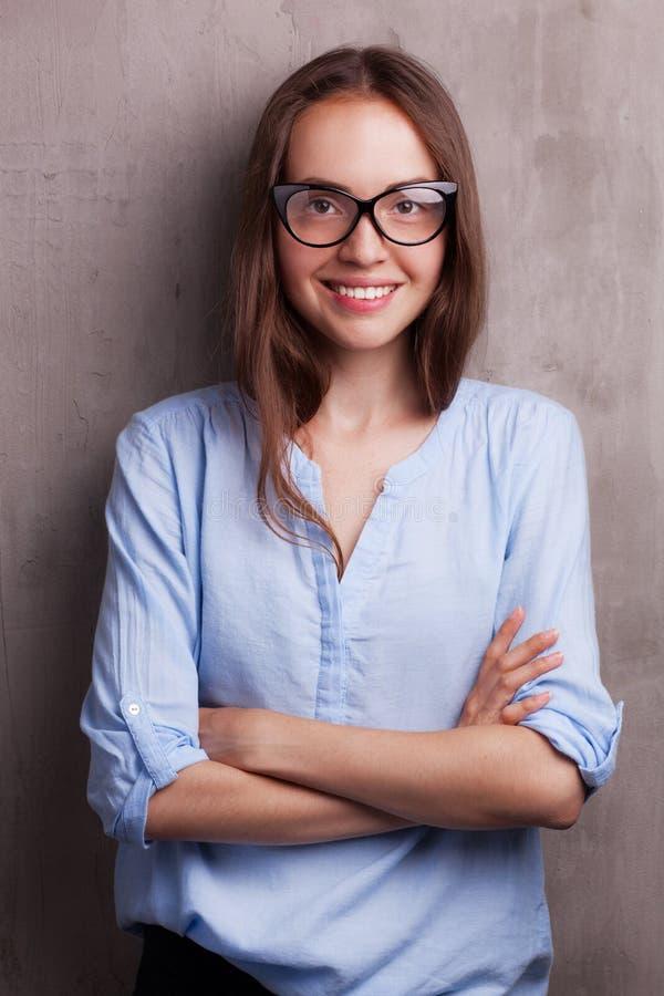 Πορτρέτο της όμορφης ευτυχούς νέας γυναίκας που φορά τα γυαλιά κοντά στον γκρίζο τοίχο grunge στοκ φωτογραφία με δικαίωμα ελεύθερης χρήσης