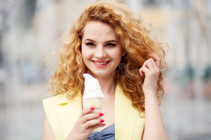 Πορτρέτο της όμορφης ευτυχούς χαμογελώντας συναισθηματικής νέας γυναίκας με τη μακριά σγουρή τρίχα που τρώει το εύγευστο παγωτό στοκ εικόνα με δικαίωμα ελεύθερης χρήσης