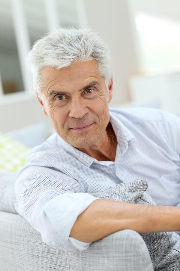 Πορτρέτο της όμορφης ηλικιωμένης χαλάρωσης ατόμων στον καναπέ στοκ φωτογραφίες