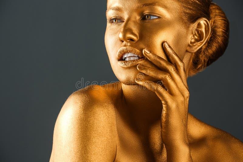 Πορτρέτο της όμορφης κυρίας με το χρυσό χρώμα στο δέρμα στο γκρίζο κλίμα στοκ εικόνα με δικαίωμα ελεύθερης χρήσης