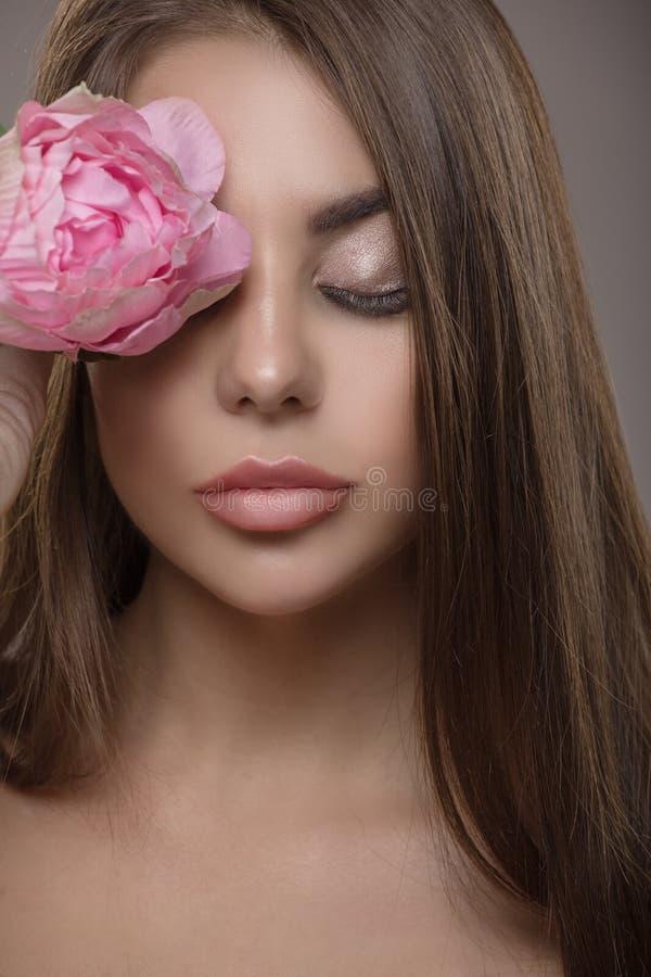 Πορτρέτο της όμορφης λαμπρής ευθείας τρίχας γυναικών και των ιδιαίτερων προσοχών Λουλούδι στοκ εικόνα