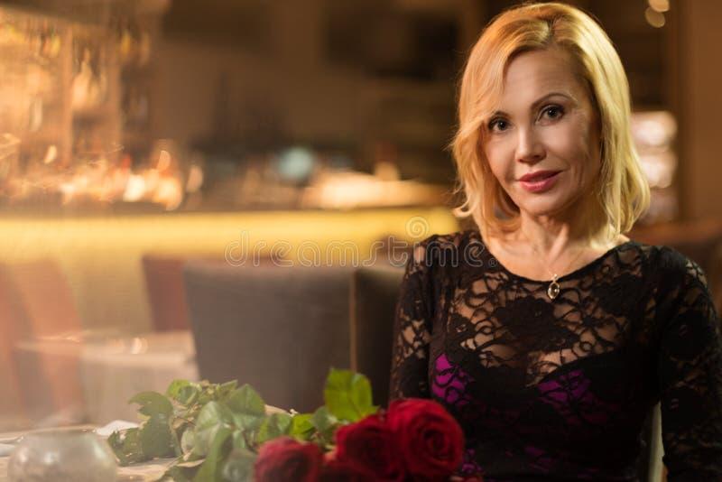 Πορτρέτο της όμορφης μέσης ηλικίας γυναίκας με την ανθοδέσμη των κόκκινων τριαντάφυλλων στο εστιατόριο στοκ φωτογραφία με δικαίωμα ελεύθερης χρήσης