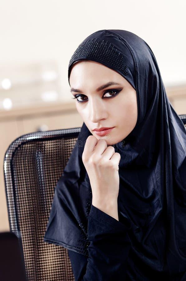 Πορτρέτο της όμορφης μουσουλμανικής συνεδρίασης γυναικών σε μια καρέκλα γραφείων στοκ εικόνα με δικαίωμα ελεύθερης χρήσης