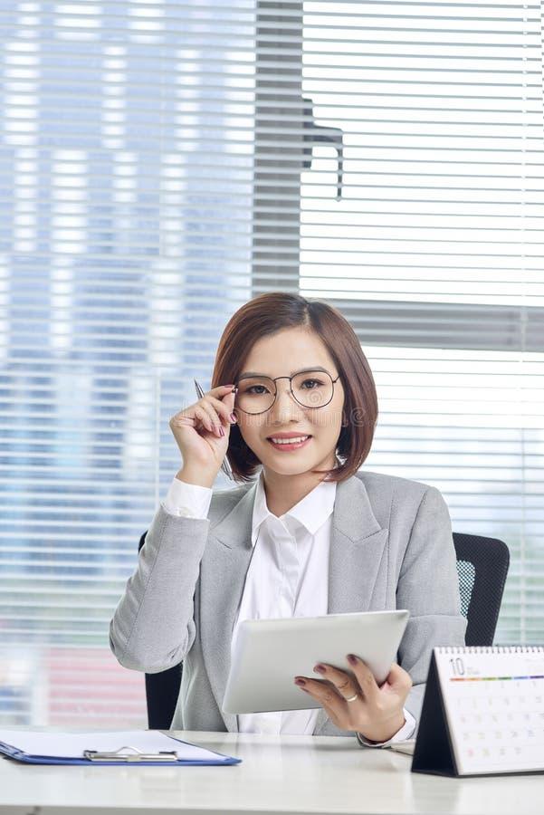 Πορτρέτο της όμορφης νέας ασιατικής επιχειρησιακής γυναίκας που κάθεται και που χρησιμοποιεί μια ταμπλέτα πίσω από τον πίνακα στο στοκ εικόνες