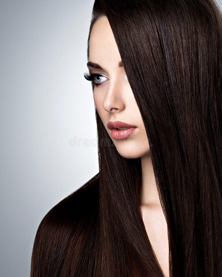 Πορτρέτο της όμορφης νέας γυναίκας με την πολύ ευθεία καφετιά τρίχα στοκ εικόνες με δικαίωμα ελεύθερης χρήσης
