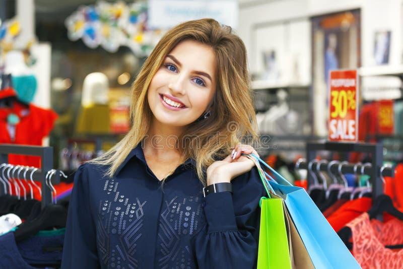Πορτρέτο της όμορφης νέας γυναίκας με τις τσάντες αγορών στον ιματισμό στοκ εικόνα