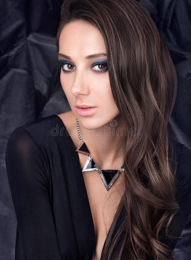 Πορτρέτο της όμορφης νέας γυναίκας με το αισθησιακό βλέμμα στο μαύρο φόρεμα στοκ εικόνες