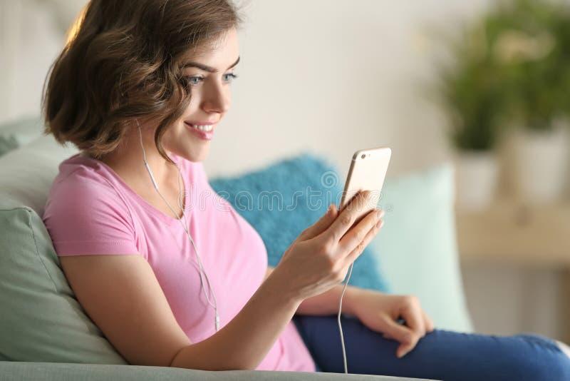 Πορτρέτο της όμορφης νέας γυναίκας με το κινητό τηλέφωνο που ακούει τη μουσική στο σπίτι στοκ εικόνες με δικαίωμα ελεύθερης χρήσης