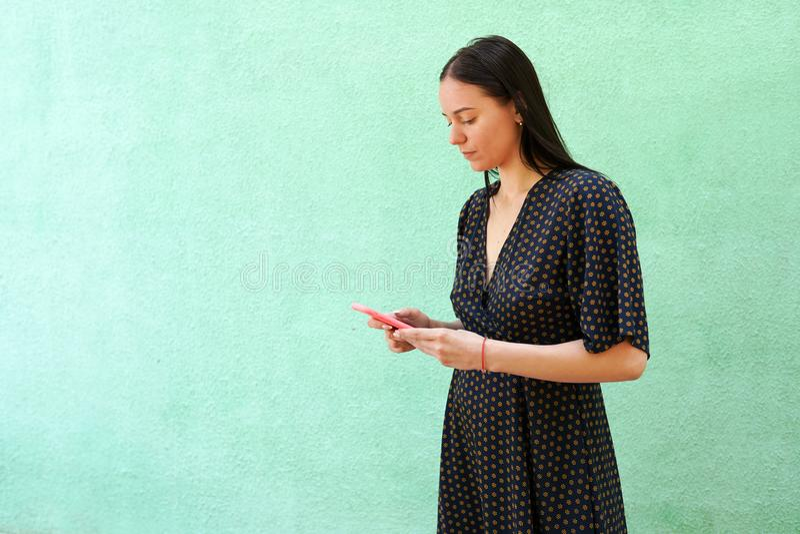 Πορτρέτο της όμορφης νέας γυναίκας που κρατά το έξυπνο τηλέφωνο στο πράσινο υπόβαθρο με το διάστημα αντιγράφων στοκ εικόνες