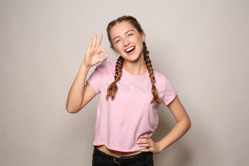 Πορτρέτο της όμορφης νέας γυναίκας που παρουσιάζει ΕΝΤΑΞΕΙ χειρονομία στο ελαφρύ υπόβαθρο στοκ εικόνες