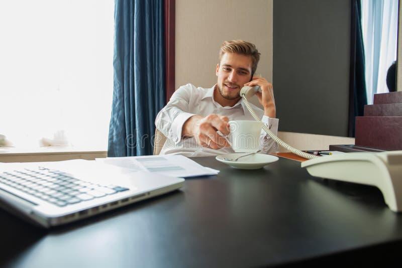 Πορτρέτο της όμορφης νέας ομιλίας επιχειρηματιών τηλεφωνικώς και της χρησιμοποίησης του lap-top εργαζόμενων στο άνετο δωμάτιο ξεν στοκ εικόνες