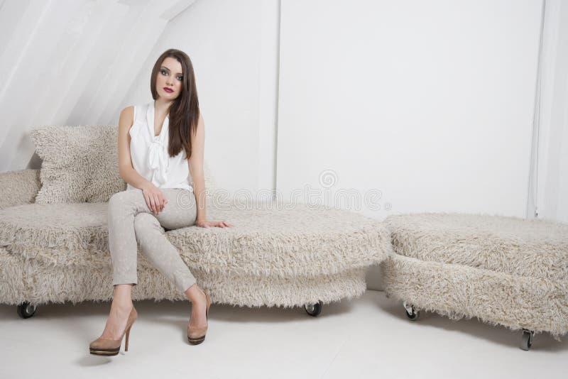 Πορτρέτο της όμορφης νέας συνεδρίασης γυναικών στον καναπέ στοκ εικόνες