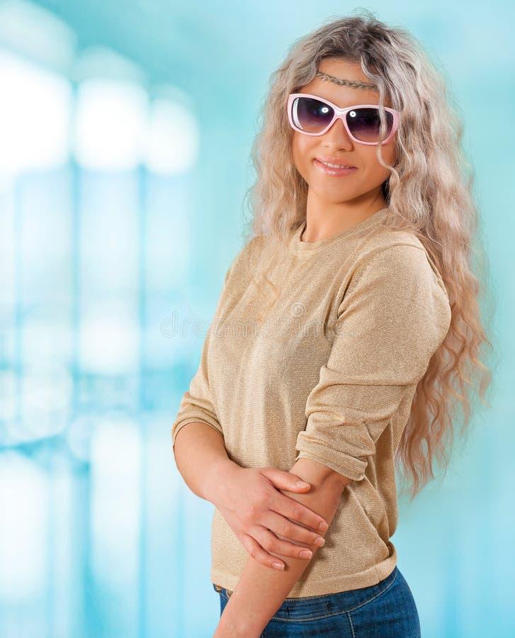 Πορτρέτο της όμορφης νέας χαμογελώντας μόνιμης γυναίκας στο υπόβαθρο στοκ φωτογραφία με δικαίωμα ελεύθερης χρήσης