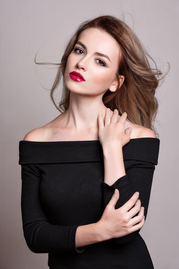 Πορτρέτο της όμορφης ξανθής γυναίκας με το σγουρό hairstyle και το φωτεινό makeup, τέλειο δέρμα, skincare, SPA, cosmetology Προκλ στοκ φωτογραφία
