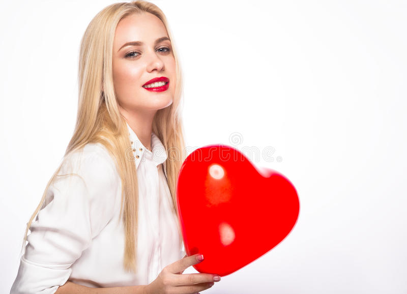 Πορτρέτο της όμορφης ξανθής γυναίκας με το φωτεινό makeup και την κόκκινη καρδιά υπό εξέταση κόκκινος αυξήθηκε στοκ φωτογραφία με δικαίωμα ελεύθερης χρήσης