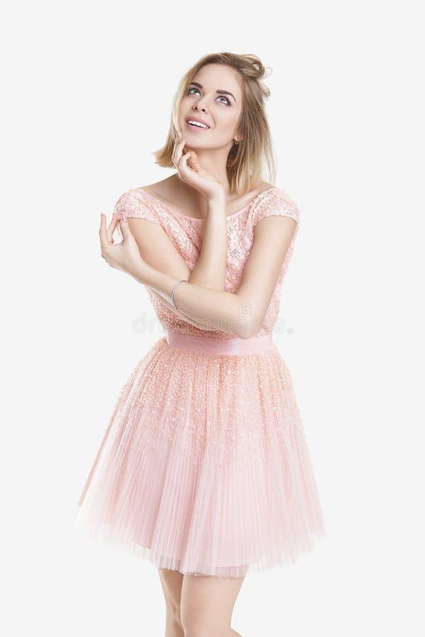 Πορτρέτο της όμορφης ξανθής γυναίκας ονείρου στο ρόδινο φόρεμα κοκτέιλ στο γκρίζο υπόβαθρο στοκ φωτογραφία