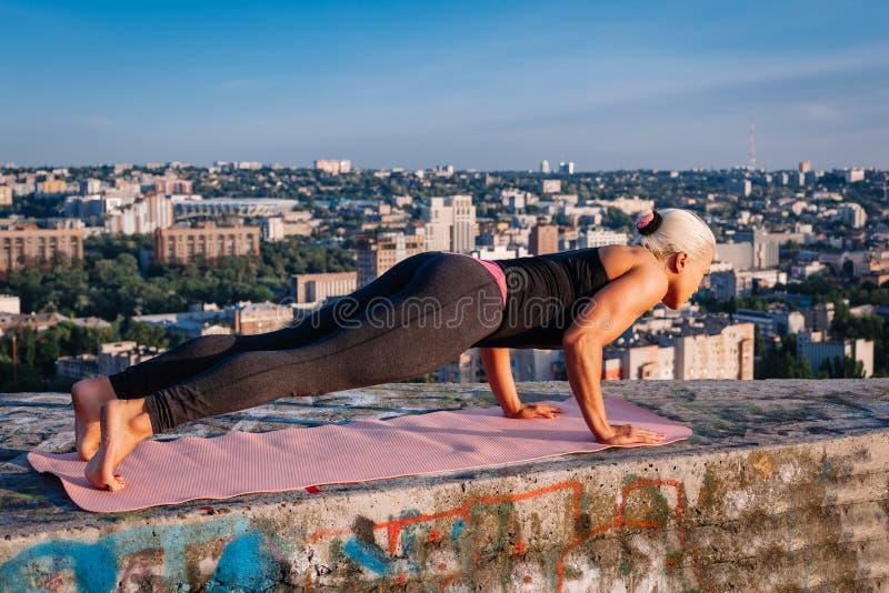 Πορτρέτο της όμορφης ξανθής ισχυρής γυναίκας sportwear να κάνει workout ώθηση-UPS στη στέγη ενός ουρανοξύστη επάνω από τη μεγάλη  στοκ εικόνα με δικαίωμα ελεύθερης χρήσης