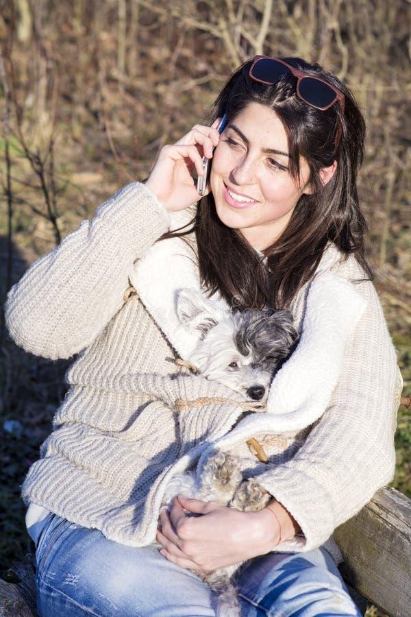 Πορτρέτο της όμορφης ομιλίας γυναικών στο τηλέφωνο και του αγκαλιάσματος του σκυλιού της στοκ φωτογραφία με δικαίωμα ελεύθερης χρήσης