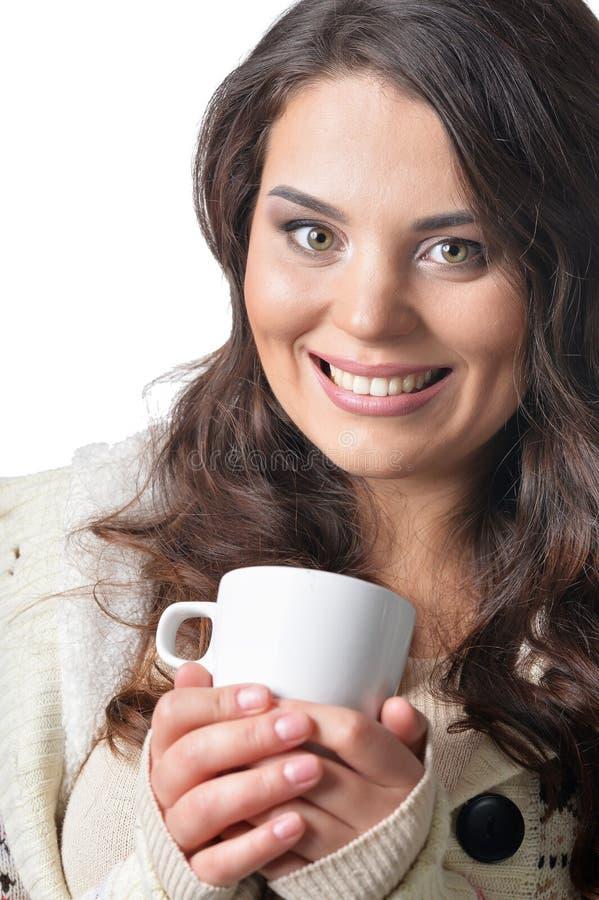 Πορτρέτο της όμορφης σγουρής γυναίκας που φορά το θερμό φλυτζάνι εκμετάλλευσης ιματισμού που απομονώνεται στοκ φωτογραφία