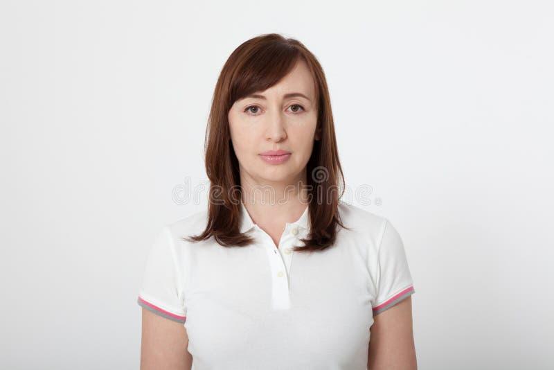 Πορτρέτο της όμορφης σοβαρής γυναίκας brunette στην κενή άσπρη μπλούζα με το διάστημα αντιγράφων στο άσπρο υπόβαθρο Χλεύη επάνω στοκ φωτογραφία