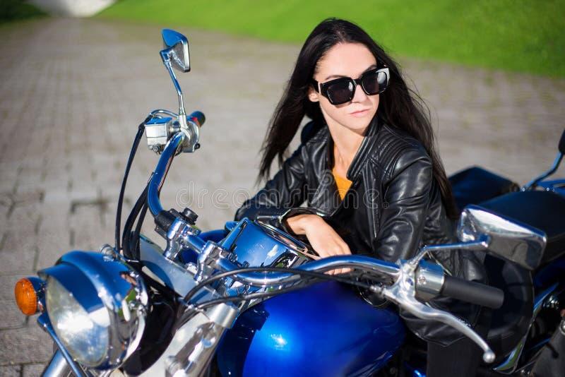 Πορτρέτο της όμορφης συνεδρίασης γυναικών στην αναδρομική μοτοσικλέτα στοκ φωτογραφίες