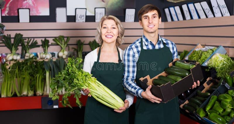Πορτρέτο της ώριμης γυναίκας και του νεαρού άνδρα που εργάζονται στο παντοπωλείο στοκ εικόνες