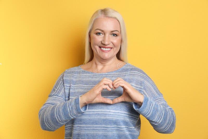 Πορτρέτο της ώριμης γυναίκας που κατασκευάζει την καρδιά με τα χέρια της στοκ εικόνες με δικαίωμα ελεύθερης χρήσης