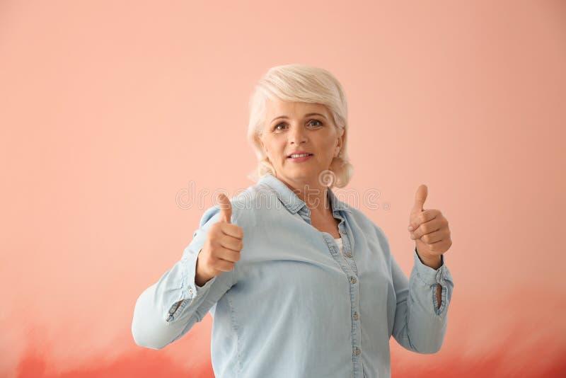 Πορτρέτο της ώριμης γυναίκας που παρουσιάζει αντίχειρας-επάνω στο υπόβαθρο χρώματος στοκ φωτογραφία με δικαίωμα ελεύθερης χρήσης