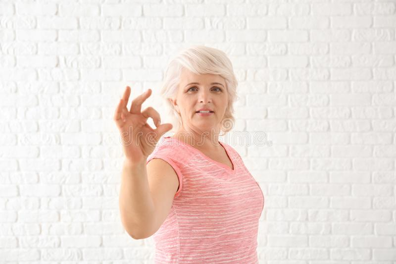Πορτρέτο της ώριμης γυναίκας που παρουσιάζει ΕΝΤΑΞΕΙ χειρονομία στο άσπρο υπόβαθρο στοκ εικόνες