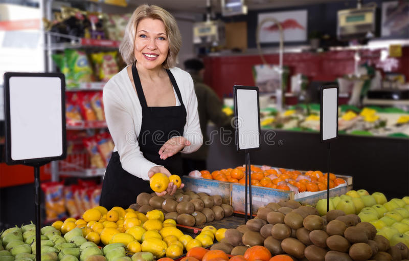 Πορτρέτο της ώριμης γυναίκας που προσφέρει τα φρούτα στο παντοπωλείο στοκ εικόνες
