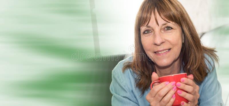 Πορτρέτο της ώριμης γυναίκας που χαμογελά και που κρατά μια κούπα στοκ εικόνες