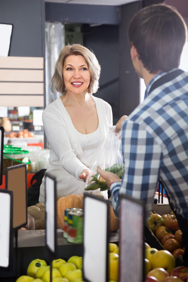 Πορτρέτο της ώριμης ξανθής γυναίκας που αγοράζει το πράσινο πιπέρι στο παντοπωλείο στοκ εικόνα με δικαίωμα ελεύθερης χρήσης