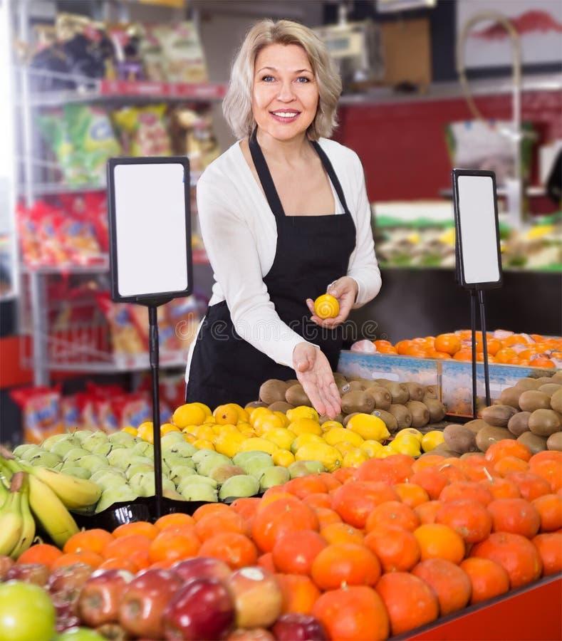 Πορτρέτο της ώριμης ξανθής γυναίκας που προσφέρει τα φρούτα στο παντοπωλείο στοκ φωτογραφία