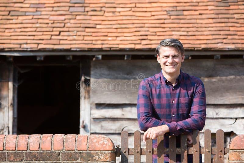 Πορτρέτο της Farmer που κοιτάζει πέρα από τον τοίχο του αγροτικού κτηρίου στοκ φωτογραφία