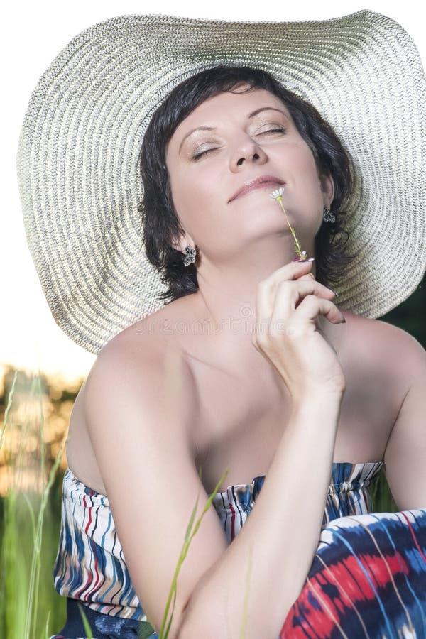 Πορτρέτο τοποθέτησης γυναικών χαμόγελου της καυκάσιας Brunette στο μεγάλο στρογγυλό καπέλο στοκ εικόνα με δικαίωμα ελεύθερης χρήσης