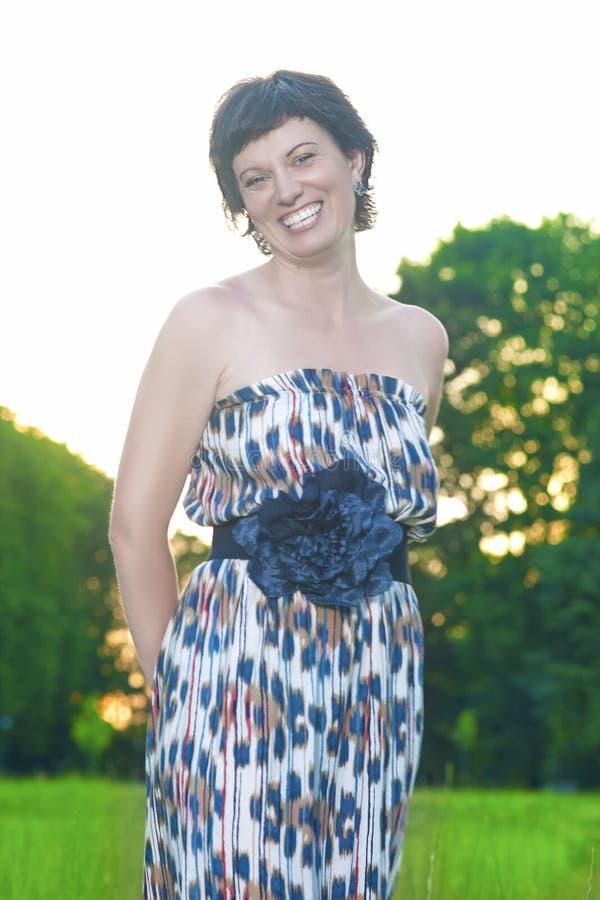 Πορτρέτο τοποθέτησης ευτυχών και γυναικών χαμόγελου της καυκάσιας Brunette υπαίθρια στο ηλιοβασίλεμα στοκ εικόνες