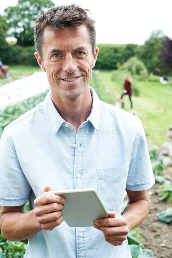 Πορτρέτο του άνδρα γεωργικός εργαζόμενος που χρησιμοποιεί την ψηφιακή ταμπλέτα στη Fie στοκ φωτογραφία