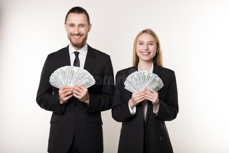 Πορτρέτο του άνδρα και της γυναίκας στο μαύρο ανεμιστήρα εκμετάλλευσης κοστουμιών των χρημάτων δολαρίων που χαμογελούν και που εξ στοκ φωτογραφία