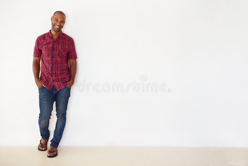 Πορτρέτο του άνετα ντυμένου ατόμου που κλίνει ενάντια στον άσπρο τοίχο στοκ φωτογραφία με δικαίωμα ελεύθερης χρήσης