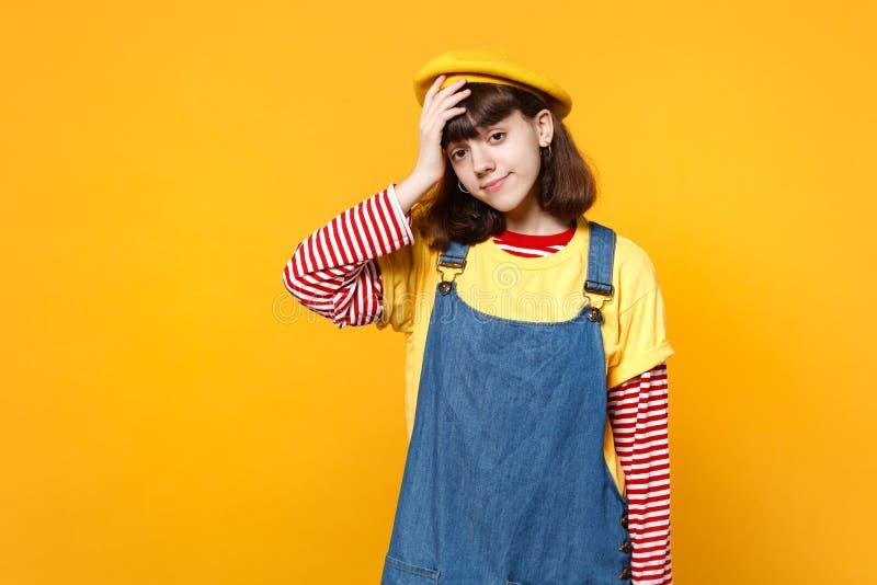 Πορτρέτο του έξυπνου εφήβου κοριτσιών γαλλικά beret και το τζιν sundress που βάζουν το χέρι στο κεφάλι που απομονώνεται στον κίτρ στοκ εικόνα