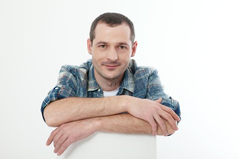 Πορτρέτο του έξυπνου σοβαρού όμορφου ατόμου στη συνεδρίαση πουκάμισων στο σπίτι στοκ φωτογραφίες