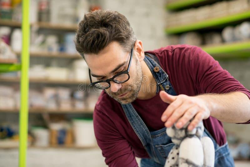 Πορτρέτο του αγγειοπλάστη που ντύνεται σε μια ποδιά που λειτουργεί στο γλυπτό αργίλου στο φωτεινό κεραμικό εργαστήριο στοκ εικόνα με δικαίωμα ελεύθερης χρήσης
