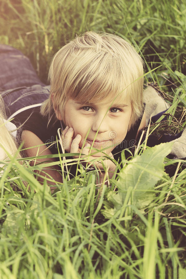 Πορτρέτο του αγοριού παιδιών στη χλόη υπαίθρια στοκ εικόνα