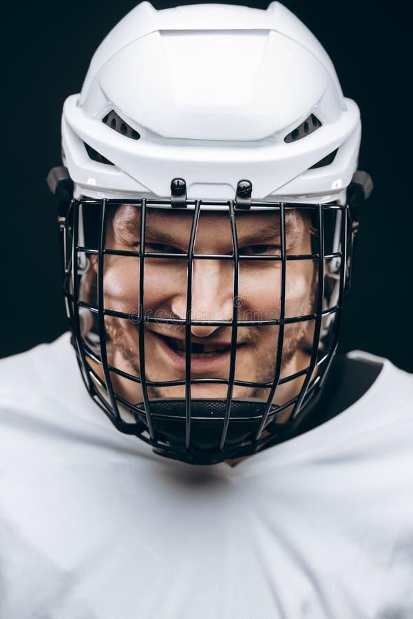 Πορτρέτο του αθλητικού τύπου στο χόκεϋ ομοιόμορφο πέρα από το μαύρο υπόβαθρο στοκ φωτογραφία με δικαίωμα ελεύθερης χρήσης