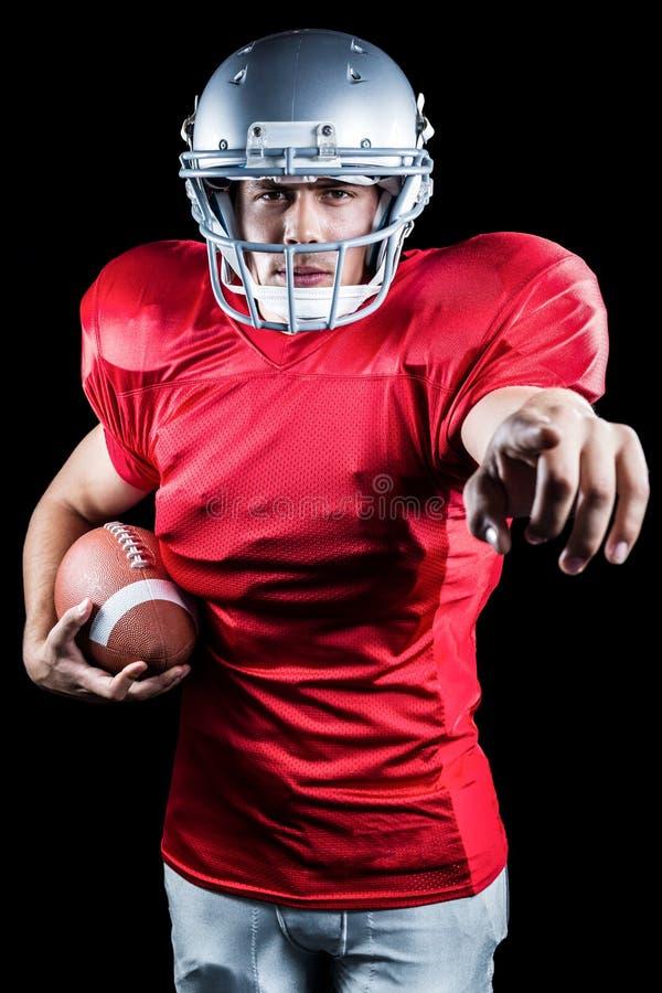 Πορτρέτο του αθλητικού τύπου που δείχνει κρατώντας το αμερικανικό ποδόσφαιρο στοκ εικόνα