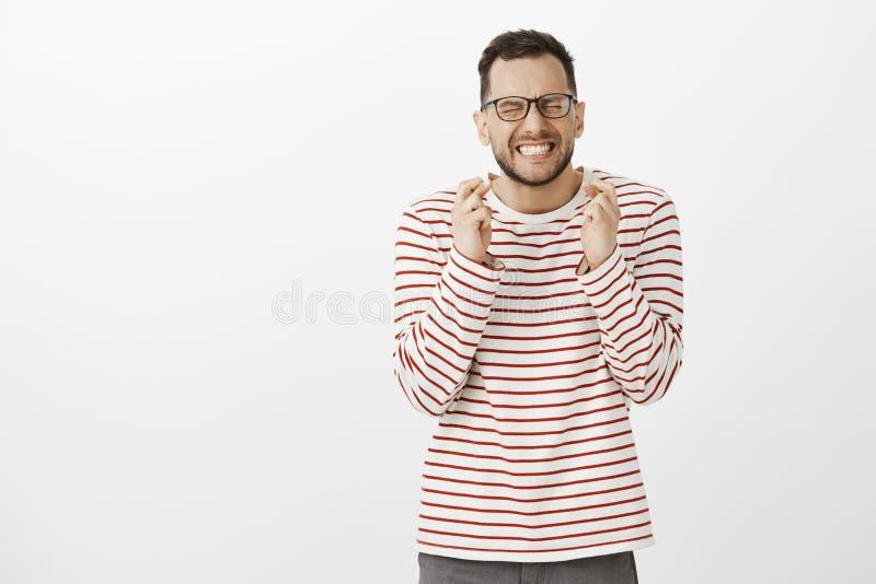 Πορτρέτο του αισιόδοξου όμορφου αρσενικού προτύπου στα μαύρα καθιερώνοντα τη μόδα γυαλιά, clenchign πυγμές και ιδιαίτερες προσοχέ στοκ φωτογραφίες