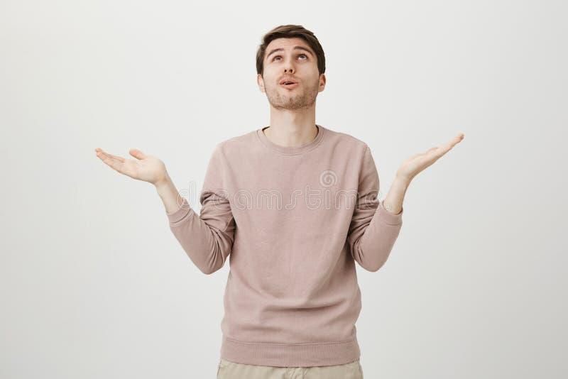 Πορτρέτο του ανακουφισμένου όμορφου νεαρού άνδρα με το χαριτωμένο κούρεμα που ανατρέχει με τους αυξημένους φοίνικες σαν λέγοντας  στοκ φωτογραφία με δικαίωμα ελεύθερης χρήσης